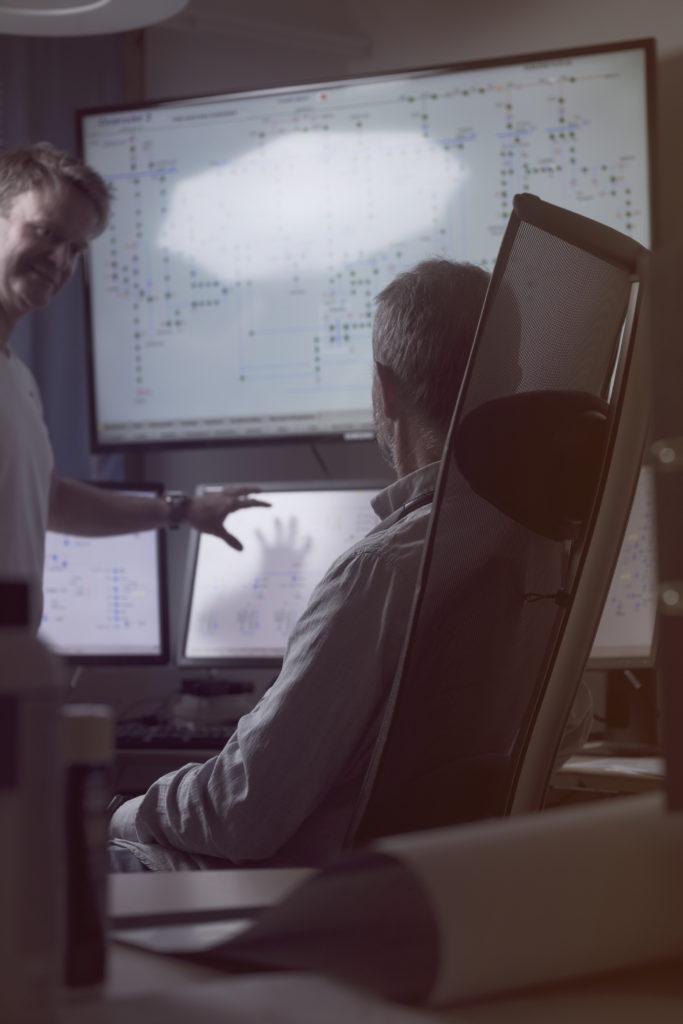 Illustrasjonsfoto av to ingeniører på kontor ved en stor overvåkningsskjerm.